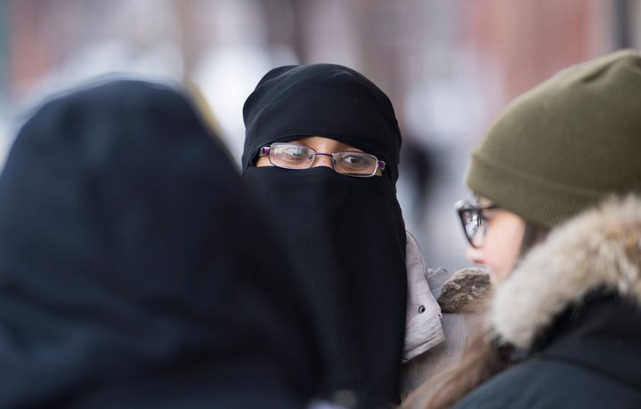 People rally outside the Khadijah Islamic Centre in the Montreal borough of Pointe-Saint-Charles, Friday, Feb. 3, 2017, in a show of support after vandals broke a window and pelted the building with eggs.