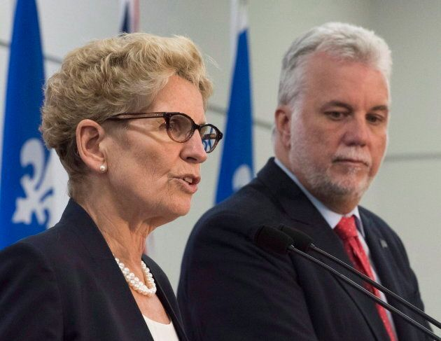 Ontario Premier Kathleen Wynne shown speaking at a news conference next to Quebec Premier Philippe on...