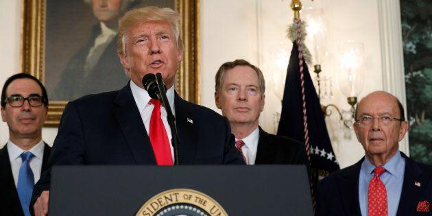 U.S. President Donald Trump, flanked by Treasury Secretary Steven Mnuchin (left), U.S. Trade Representative...