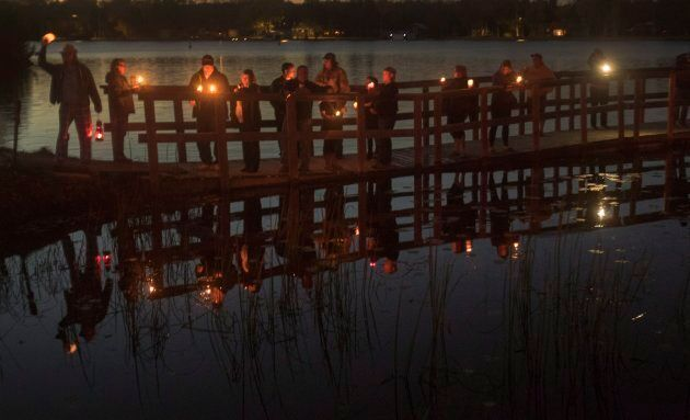 Fans of the Tragically Hip gather for a candlelight vigil by the water's edge in Bobcaygeon, Ont. to...