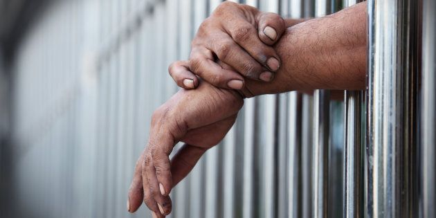 A man's hands are shown in jail. Judge Marc Chisholm has sentenced a Halifax man to eight months in jail,...