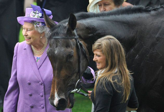 Queen Elizabeth smiles as she stands with her horse Estimate after it won the Gold Cup during Ladies'...
