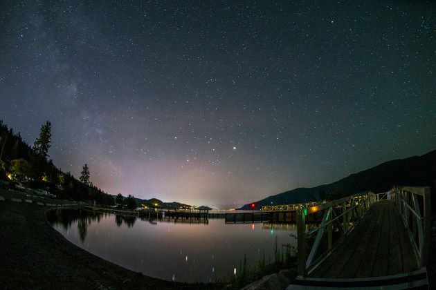A calm Okanagan Lake at night beneath the stars of the Milky Way galaxy.