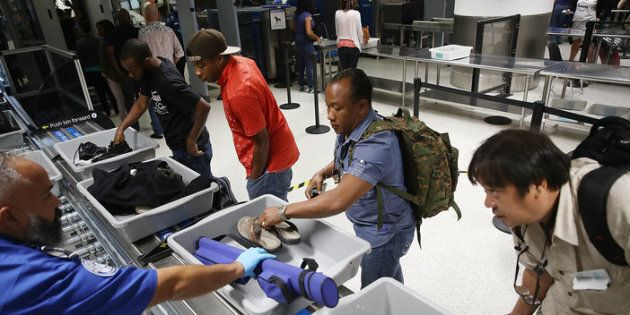 Travelers use automated screening lanes at Miami International Airport.