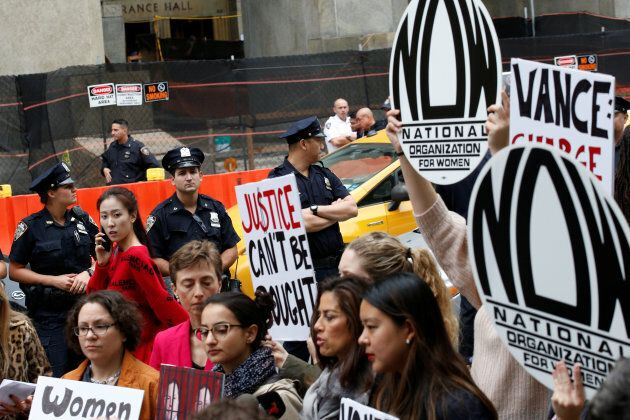 NYPD officers watch National Organization for Women members rally to call upon Manhattan District Attorney...