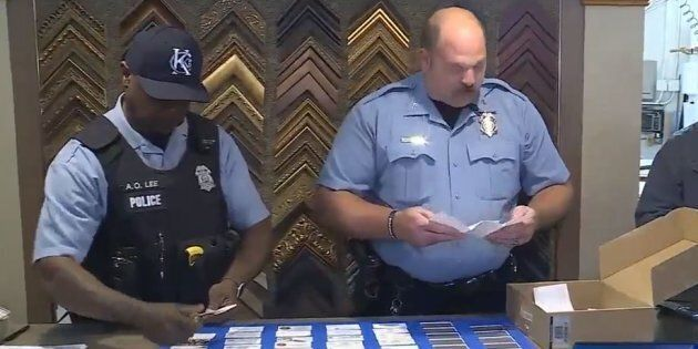 Officers from Kansas City, Kansas Police Department collecting business cards to give to a family of...