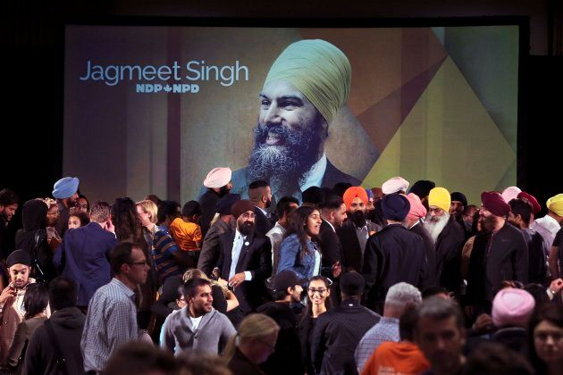 A photograph of Jagmeet Singh is projected on a screen behind a full stage of supporters after Singh...