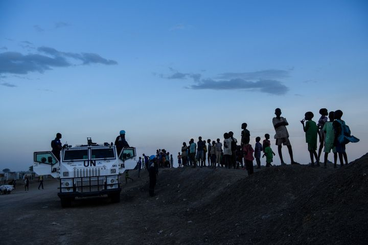 Children gather around a United Nations armoured personnel carrier as they watch tensions between different communities build up following the escalation of a dispute involving young men in the Protection of Civilians (PoC) site in Bentiu, South Sudan, Sunday, April 30, 2017.