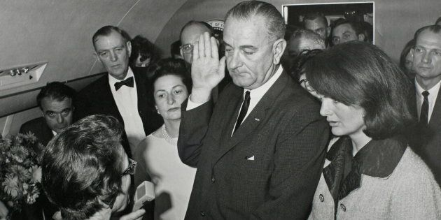 U.S. Vice President Lyndon B. Johnson taking the presidential oath of office next to President John F. Kennedy's widow first lady Jacqueline Bouvier Kennedy aboard Air Force One on November 22, 1963.