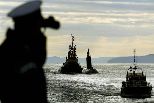 The HMCS Chicoutimi, centre, being towed to Clyde Faslane base,