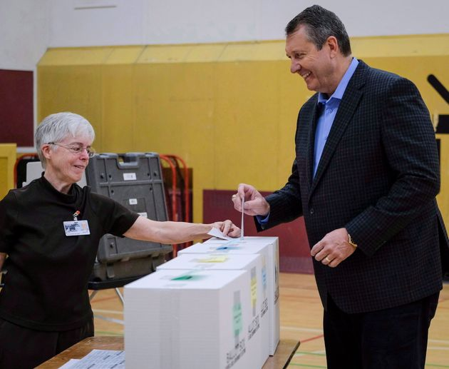 Calgary mayoral candidate Bill Smith, right, casts his vote in the municipal election at a polling station...