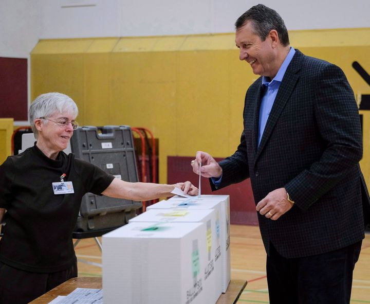 Calgary mayoral candidate Bill Smith, right, casts his vote in the municipal election at a polling station in Calgary, Alta., Monday, Oct. 16, 2017.