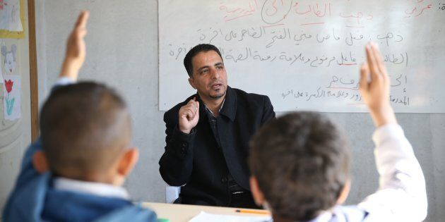44-year-old Syrian refugee Hudur Omar Ilgeya lectures the refugee children at a temporary education centre...