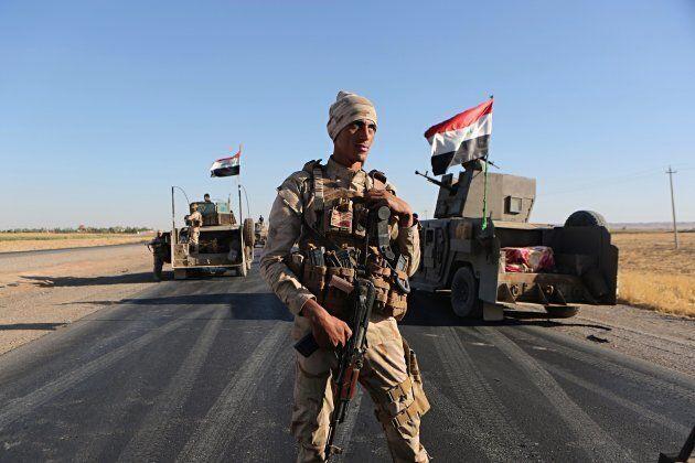 Iraqi security forces gather outside the Kurdish-held city of Altun Kupri in Iraq on Oct. 19,