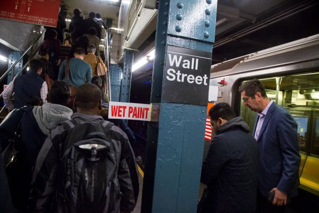 Commuters exit the Wall Street subway station near the New York Stock Exchange on