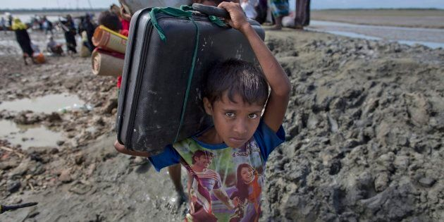 A newly arrived Rohingya Muslim boy from Myanmar walks towards a camp for refugees in Teknaf, Bangladesh...