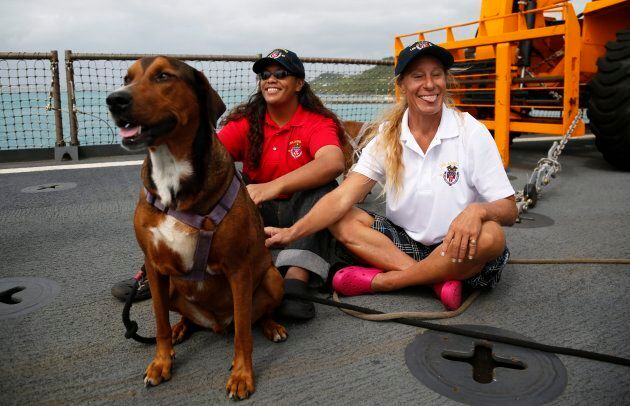 Jennifer Appel and Tasha Fuiava sit with their dogs on the deck of the USS Ashland on Oct.