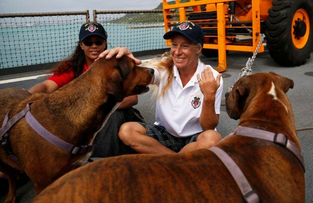 Jennifer Appel and Tasha Fuiava sit with their dogs on the deck of the USS Ashland on
