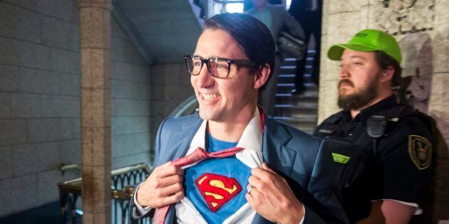 Prime Minister Justin Trudeau shows off his costume as Clark Kent, alter ego of comic book superhero Superman, as he walks through the House of Commons in Ottawa on Oct.  31, 2017.