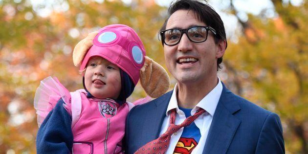 Prime Minister Justin Trudeau, dressed as Clark Kent, holds his son Hadrien, dressed as Skye from