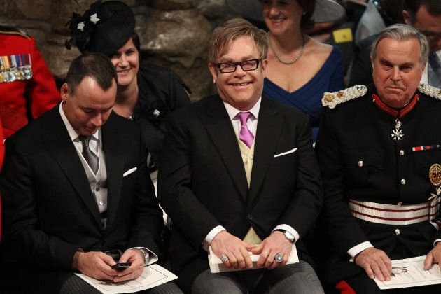 Elton John (C) and partner David Furnish (L) attend the wedding service for Britain's Prince William...