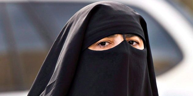 A woman wears a niqab as she walks Monday, Sept. 9, 2013 in