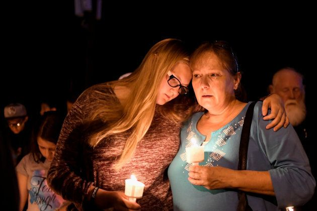 Local residents embrace during a candlelight vigil for victims of a mass shooting in a church in Sutherland...