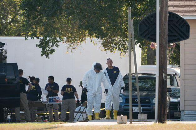 FBI officers walk behind the First Baptist Church of Sutherland Springs after a fatal shooting on Nov....