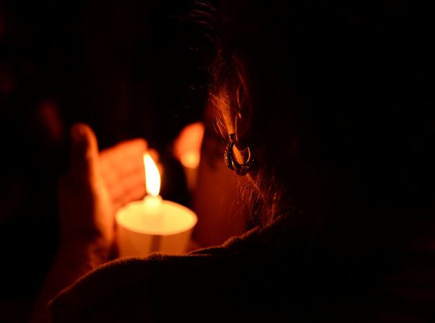 A woman attends a candle light vigil Sunday for the victims of the mass shooting at the First Baptist...
