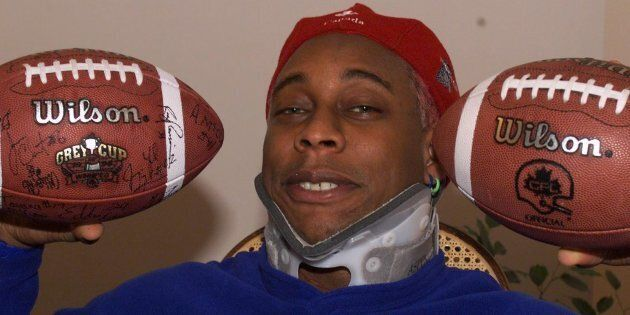 Former Calgary Stampeders linebacker Anthony McClanahan poses wearing a neckbrace and holding up two...
