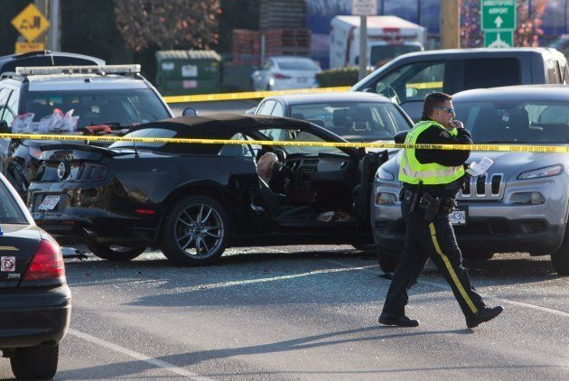 Police officers investigate the scene of a shooting that left one police officer dead in Abbotsford,...