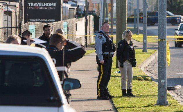 Police officers investigate the scene of a shooting that left one officer dead in Abbotsford, B.C., on...