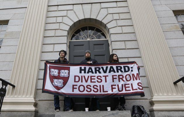 Students demanding that Harvard University divest from fossil fuels block the entrance to University...