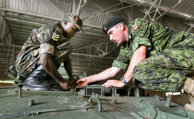A Canadian soldier, right, works with a Rwandan African Union peacekeeper during an unrelated Canadian-led training course for African troops near Thies, Senegal on Sept. 9, 2005. File photo.