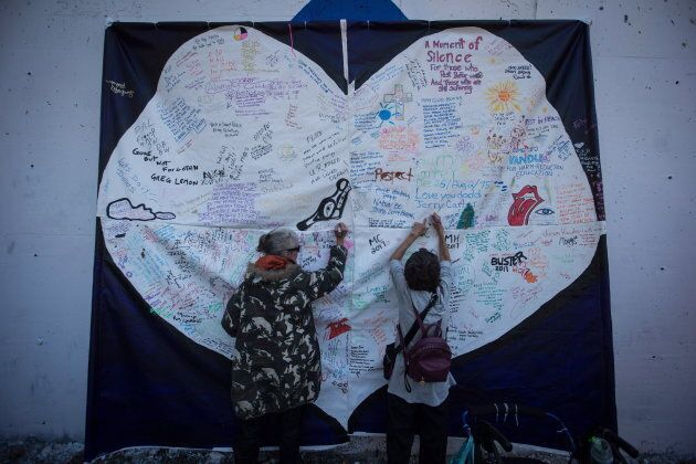 Women write messages on a banner during a memorial service to remember those who have died in B.C. as...