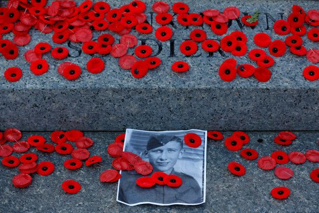 A photograph is surrounded by poppies placed on the Tomb of the Unknown Soldier following Remembrance...