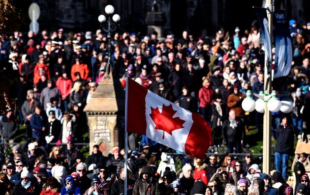 A Canadian flag flies as people line up along Wellington Street and outside Parliament Hill's East Block...