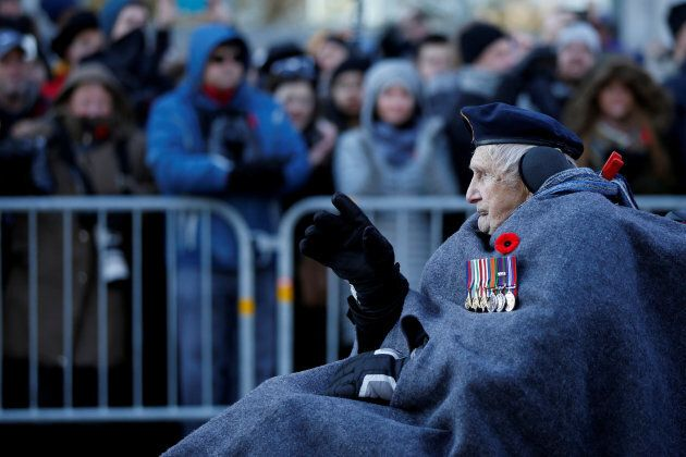 A veteran waves to the crowd as he arrives for Remembrance Day ceremonies at the National War