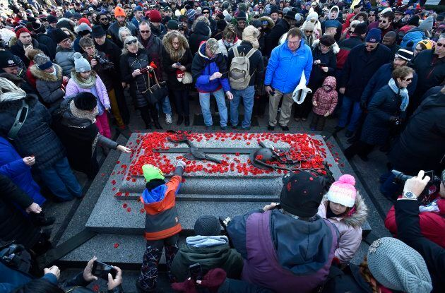 People lay poppies on the Tomb of the Unknown Soldier following the National Remembrance Day