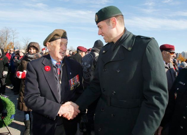 Master Corporal Andrew White speaks with Jack Commerford, 93, a veteran who landed on Juno Beach in World...