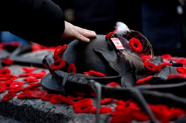 A man touches the helmet on the Tomb of the Unknown Soldier after laying a poppy following the National...