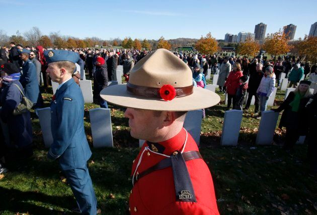 A Mountie wearing a poppy stands at attention at the National Military Cemetery during a ceremony on...
