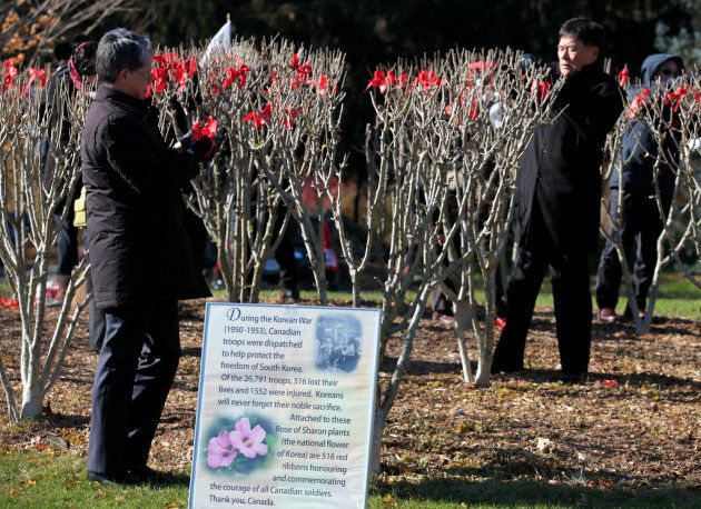 Participants tie red ribbons on Rose of Sharon trees in honor of 516 Canadian troops who lost their lives...