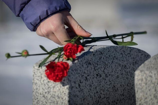 Sarah Markovich places a carnation on the grave marker of a veteran following a Remembrance Day service...