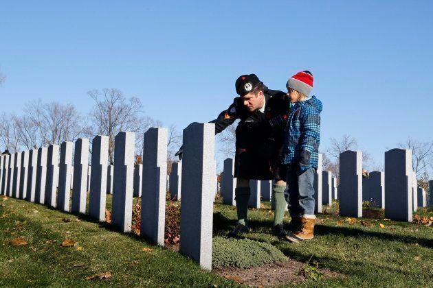 Corporal David Harding of the Cameron Highlanders and his son Silas, 8, visit the National Military Cemetery...