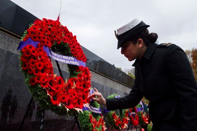 A member of the Canadian Military places a poppy on the public wreath during Remembrance Day services...
