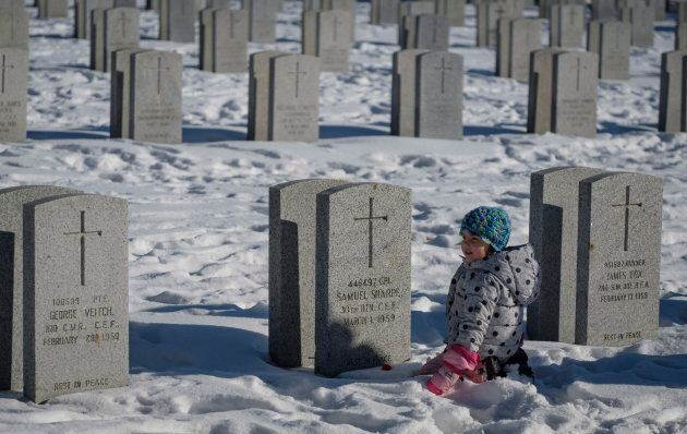 A young girl plays amongst veteran's grave markers following a Remembrance Day service in