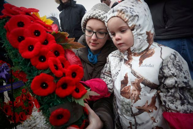 Isolde Chisholm pins her poppy to a wreath with the help of her aunt Rosemund Ragetli at a cenotaph during...