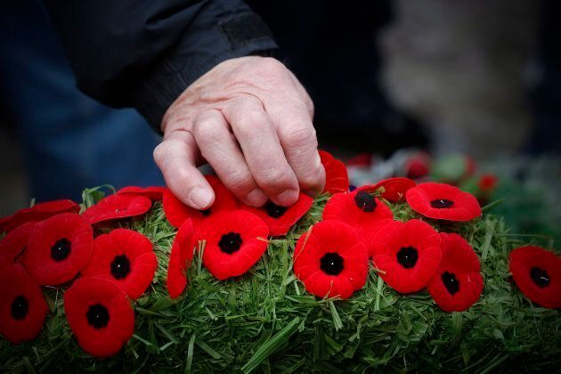 Poppies are placed on a wreath at a cenotaph during a Remembrance Day service in