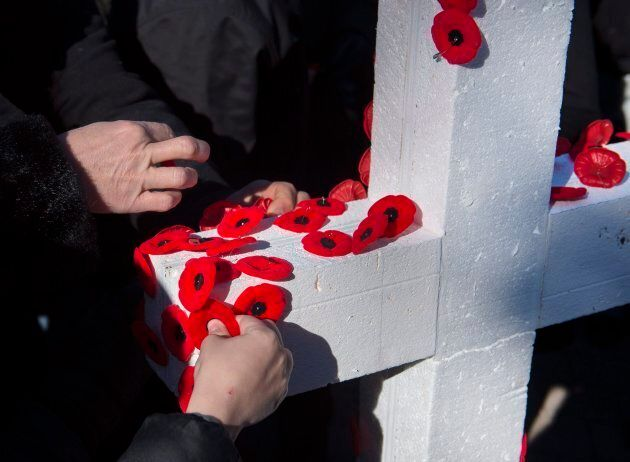 Poppies are placed on a cross during Remembrance Day ceremonies at the Grand Parade in